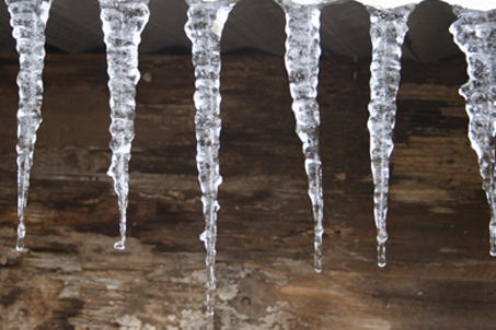 Ice hangs from the barn roof