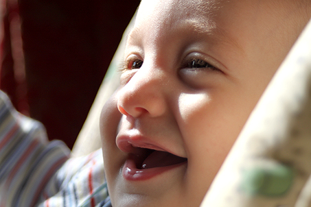 A super-close-up of Calvin near the window in his highchair