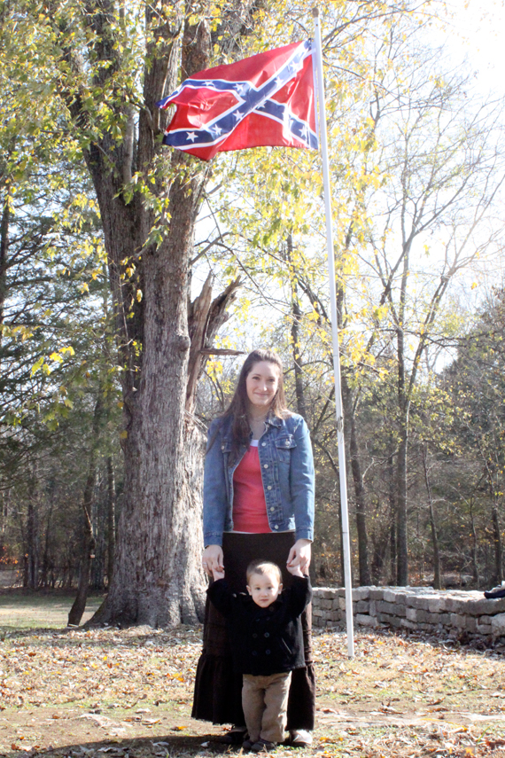 Melissa and Calvin pose under the flag in the front yard