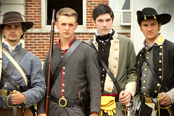 Four Confederate soldiers stand in front of the Perry County courthouse